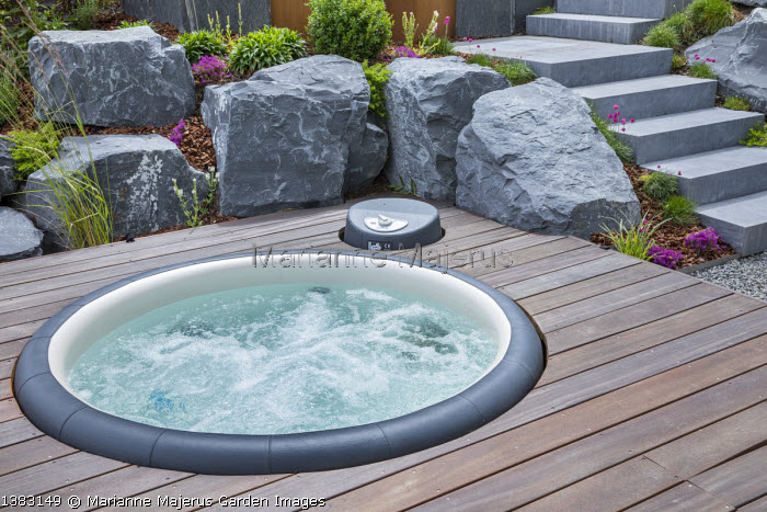 Circular hot tub, jacuzzi sunk into wooden decking, large rocks