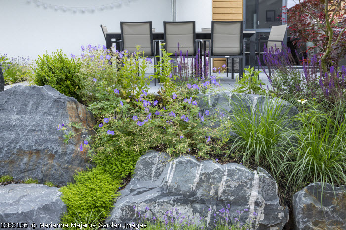 Large rocks, table and chairs on patio, geraniums