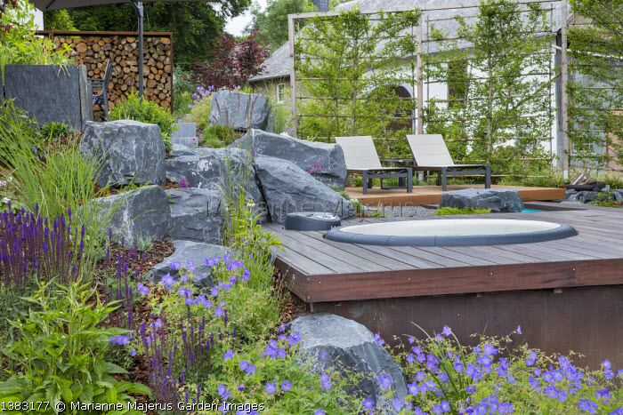 Large rocks, recliner chairs on terrace, geraniums, salvia, jacuzzi