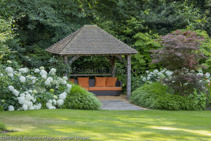 Orange cushions on seat under arbour, Hydrangea arborescens 'Annabelle', acer, Hackonechloa macra