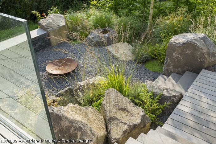 Large basalt rocks around gravel terrace, Cor-ten steel fire bowl, steps, Molinia caerulea subsp. arundinacea 'Skyracer', Ilex crenata 'Convexa'