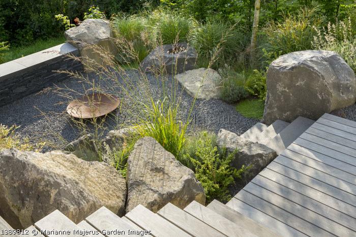 Large basalt rocks around gravel terrace, Cor-ten steel fire bowl, Molinia caerulea subsp. arundinacea 'Skyracer', Miscanthus sinensis 'Adagio', Ilex crenata 'Convexa'