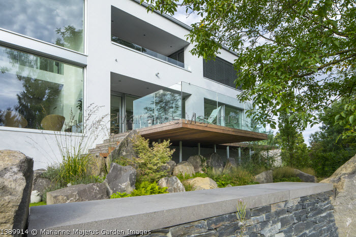 Contemporary basalt rock garden, Molinia arundinacea 'Skyracer', acer, Juglans regia, slate wall