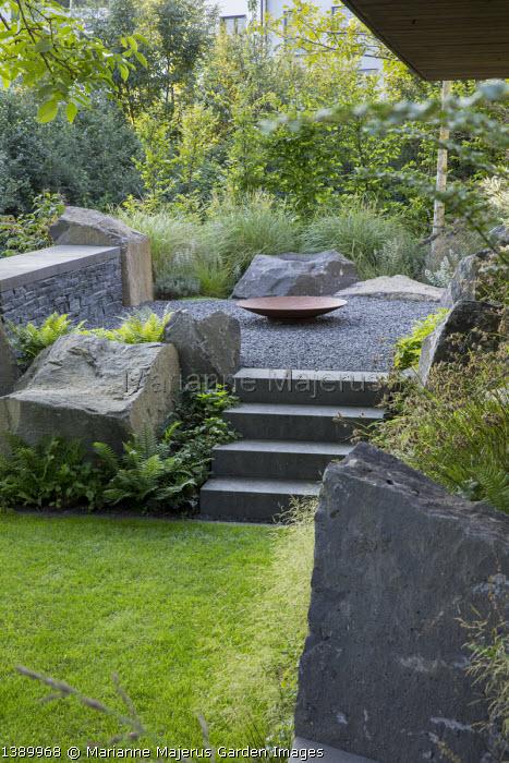Contemporary basalt rock garden, lawn, steps to Cor-ten steel fire bowl on gravel terrace, Miscanthus sinensis 'Adagio'