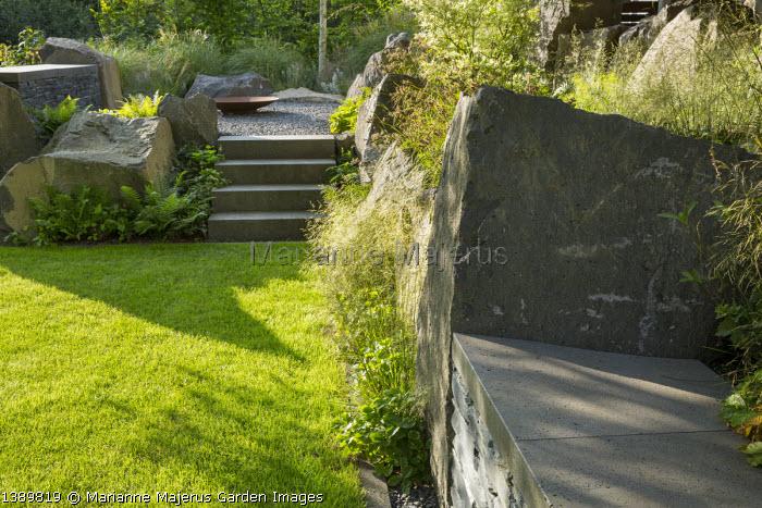 Contemporary basalt rock garden, lawn, steps to Cor-ten steel fire bowl on gravel terrace, Deschampsia cespitosa, Luzula nivea