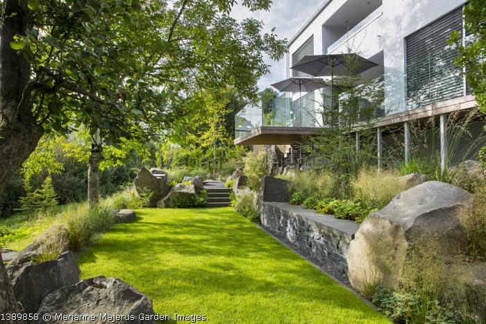 Contemporary basalt rock garden, lawn, built-in stone wall bench, Nothofagus Antarctica, Deschampsia cespitosa, Fragaria vesca 'Alexandria'