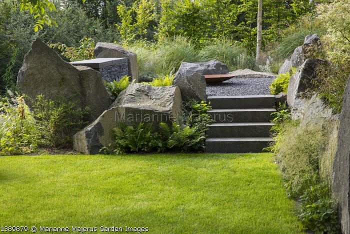 Contemporary basalt rock garden, lawn, steps to Cor-ten steel fire bowl on gravel terrace