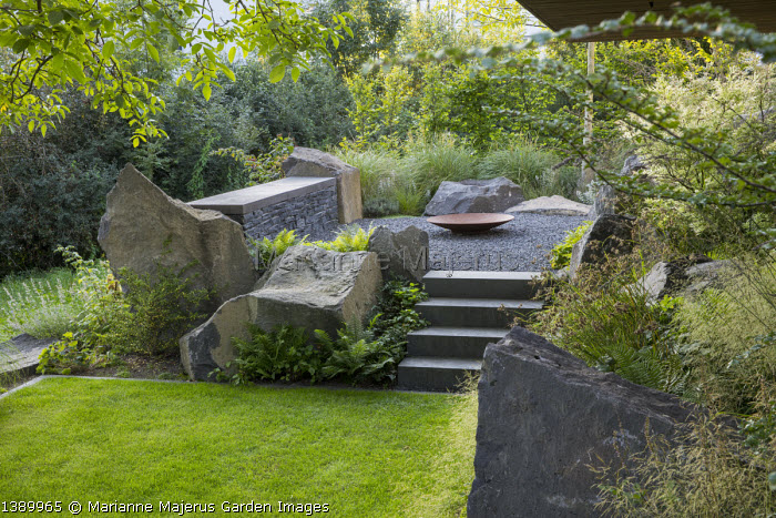 Contemporary basalt rock garden, lawn, steps to Cor-ten steel fire bowl on gravel terrace, Luzula nivea