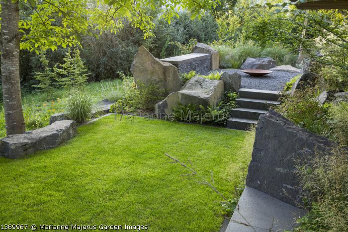 Contemporary basalt rock garden, lawn, steps to gravel terrace