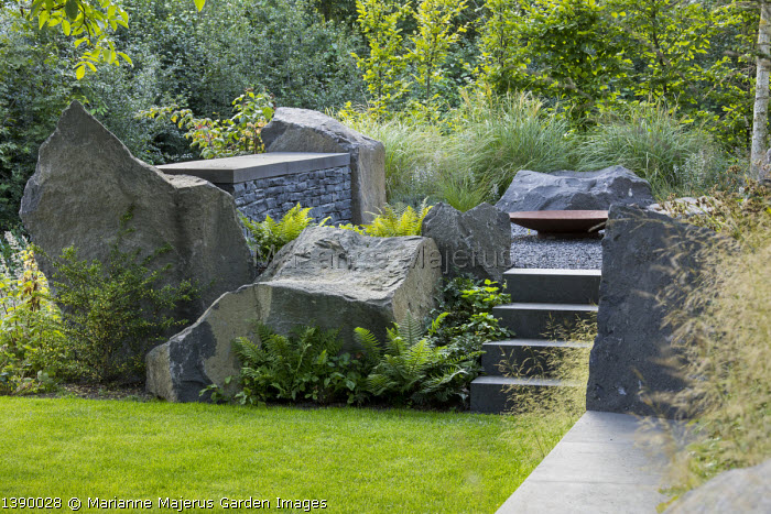 Contemporary basalt rock garden, lawn, steps to Cor-ten steel fire bowl on gravel terrace, Ilex crenata 'Convexa'