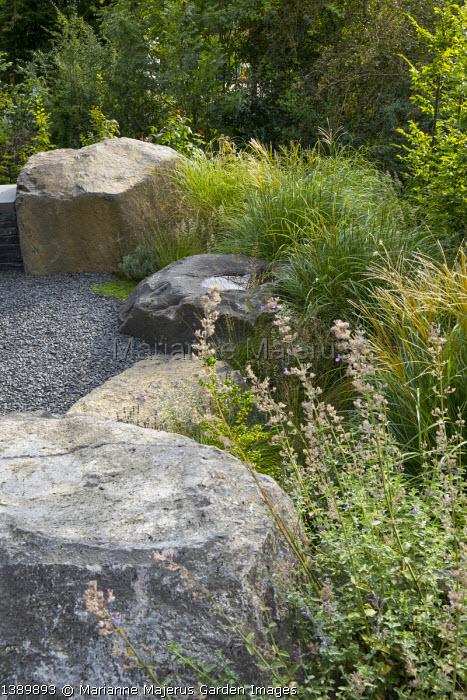 Large basalt rocks around gravel terrace, Miscanthus sinensis 'Adagio', Nepeta × faassenii 'Walker's Low'
