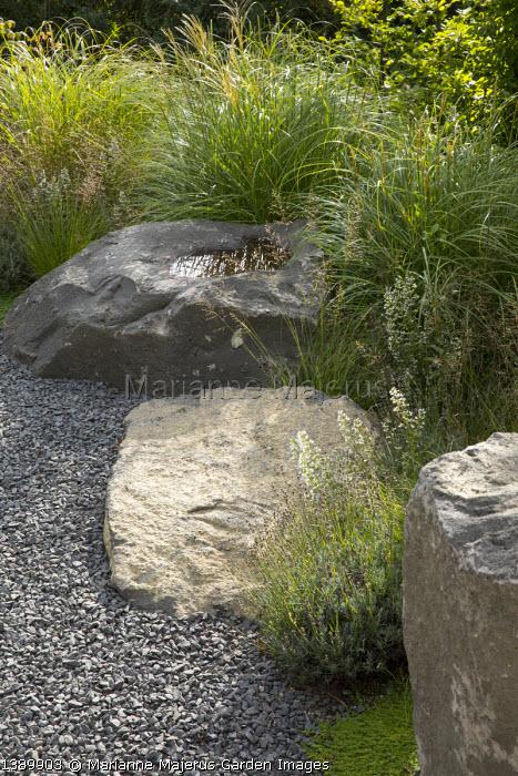 Large basalt rocks around gravel terrace, Miscanthus sinensis 'Adagio', Lavandula angustifolia 'Dwarf Blue´, Calamintha nepeta, Sporobolus heterolepis 'Cloud´