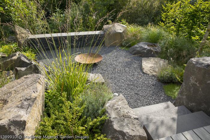 Large basalt rocks around gravel terrace, Cor-ten steel fire bowl, Molinia caerulea subsp. arundinacea 'Skyracer', Ilex crenata 'Convexa'