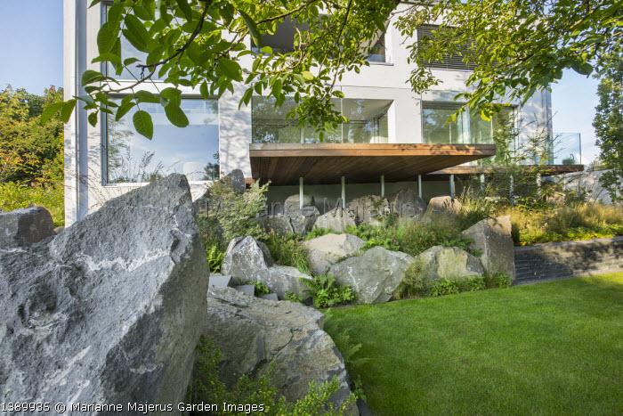 Contemporary basalt rock garden, lawn, Luzula nivea