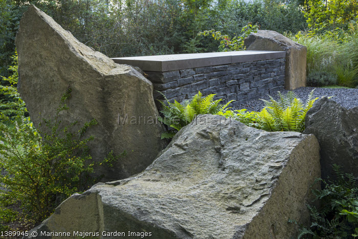 Large basalt rocks, dry-stone built-in wall bench, Ilex crenata 'Convexa'