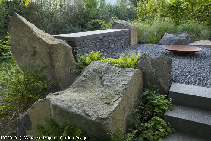 Large basalt rocks around gravel terrace, Cor-ten steel fire bowl, Ilex crenata 'Convexa'