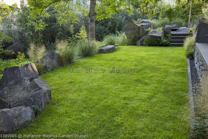 Contemporary basalt rock garden, lawn, Juglans regia