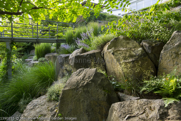 Contemporary metal platform overhanging sloping basalt rock garden, Miscanthus sinensis 'Gracillimus', Eurybia divaricata syn. Aster divaricatus, Perovskia atriplicifolia 'Blue Spire', viburnum