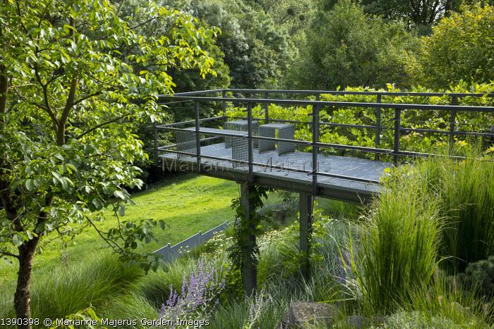 Contemporary metal platform overhanging sloping rock garden, Miscanthus sinensis 'Gracillimus', perovskia