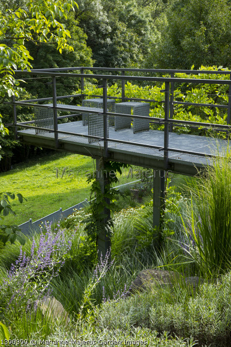 Stools on contemporary metal platform overhanging sloping rock garden, Miscanthus sinensis 'Gracillimus', Perovskia atriplicifolia 'Blue Spire'