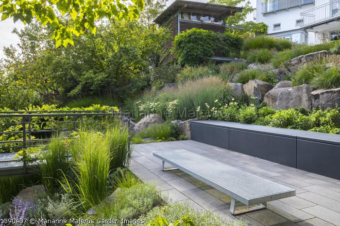Contemporary bench on stone patio, contemporary basalt rock garden, Panicum virgatum 'Heavy Metal'