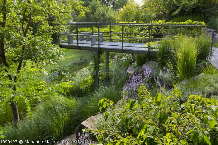 Contemporary metal platform overhanging sloping rock garden, Miscanthus sinensis 'Gracillimus', Perovskia atriplicifolia 'Blue Spire', Viburnum plicatum 'Mariesii'