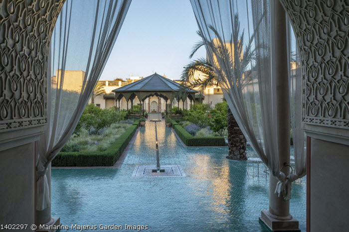 View into contemporary Islamic garden, veil curtain, borders edged with low clipped rosemary hedges, Stipa tenuissima, lemon trees, glazed green bejmat tile path, ornate arbour