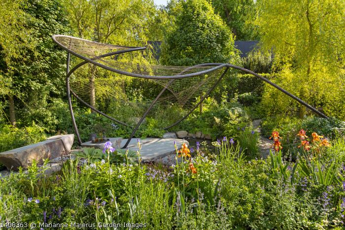 Contemporary pavilion over stream and stone terrace, Iris 'Kent Pride', Aruncus 'Guinea Fowl', Osmunda regalis, Geranium pratense 'Mrs Kendall Clark', Salix alba 'Tristis'