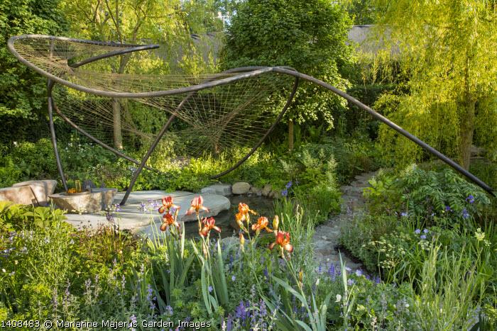 Contemporary pavilion over stream and stone terrace, Iris 'Kent Pride', Aruncus 'Guinea Fowl', Osmunda regalis, Geranium pratense 'Mrs Kendall Clark', Laser triloba