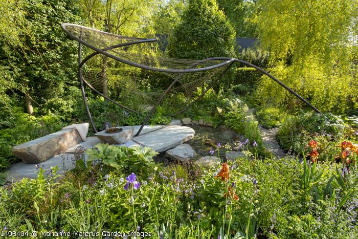 Contemporary pavilion over stream and stone terrace, Iris 'Kent Pride', Geranium pratense 'Mrs Kendall Clark', Amsonia illustris, Geum rivale, Salix alba 'Tristis'