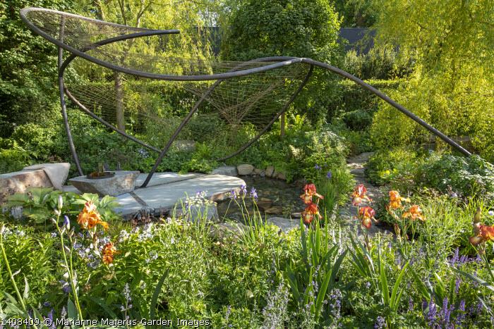 Contemporary pavilion over stream and stone terrace, Iris 'Kent Pride' and 'Carnival Time', Osmunda regalis, Geranium pratense 'Mrs Kendall Clark', Amsonia illustris, Geum rivale