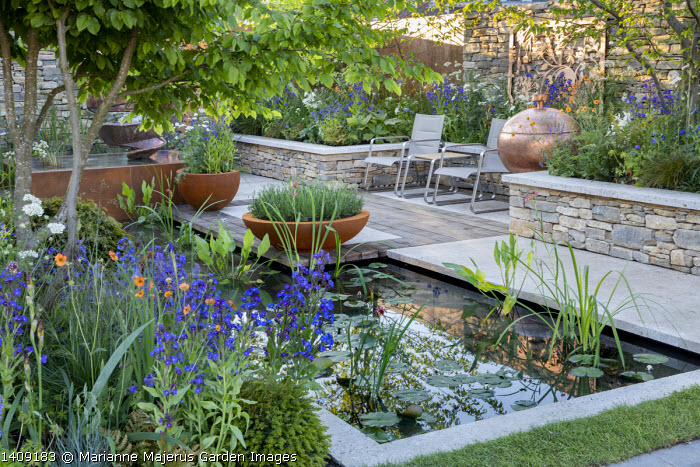 Formal water lily pond, Geum 'Totally Tangerine', Anchusa azurea 'Dropmore', chairs, stone raised bed, Lavandula angustifolia 'Alba' in large Cor-Ten steel pots