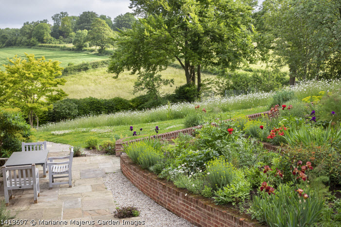 Terraced border, Papaver orientale (Goliath Group) 'Beauty of Livermere', Euphorbia griffithii 'Dixter', Iris 'Quechee', Euphorbia seguieriana subsp. niciciana, brick walls, wooden table and chairs on stone patio