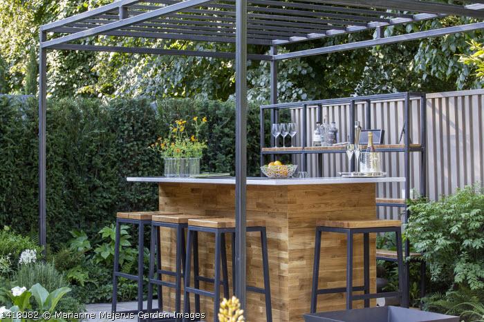 Black pergola over outdoor bar on terrace, yew hedge