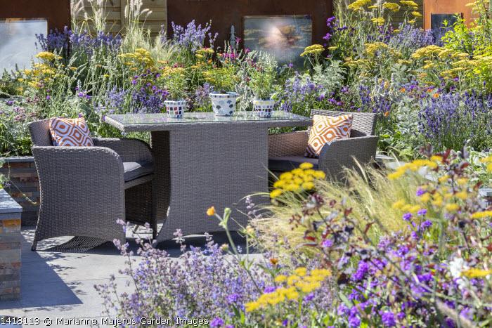 Outdoor chairs and table on stone patio, Achillea 'Terracotta', Lavandula angustifolia 'Hidcote', Lavandula x intermedia 'Edelweiss'
