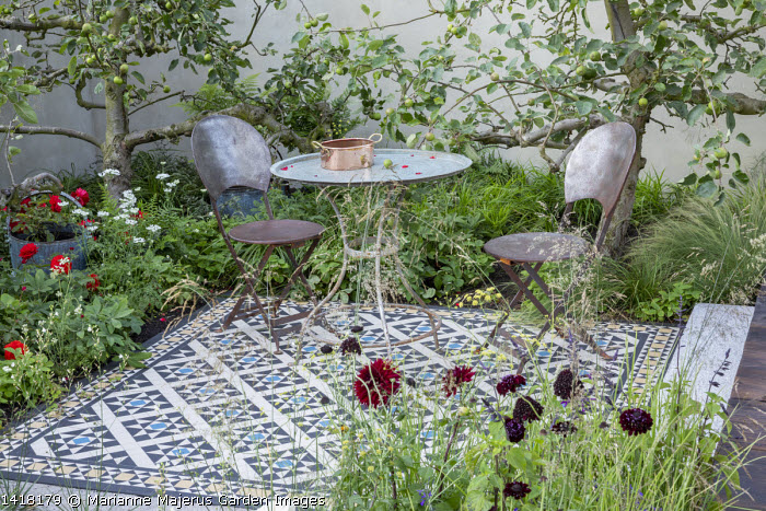 Table and chairs on mosaic tiled patio, reclaimed apple trees, Scabiosa atropurpurea 'Black Knight'