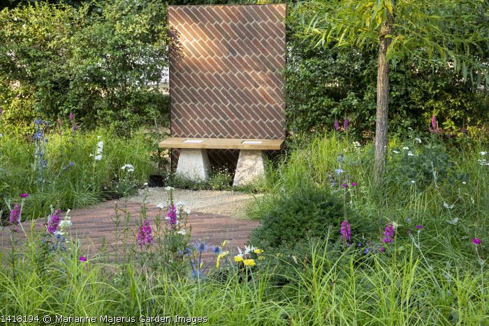 Diagonal brick screen behind bench, brick patio, Lythrum salicaria, yew mound, eryngium, achillea