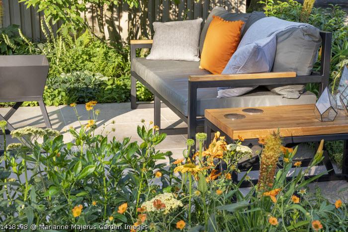 Geum 'Totally Tangerine', Achillea 'Credo', grey and orange cushions on contemporary sofa on terrace