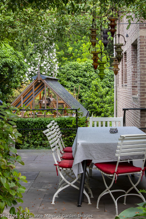 Tablecloth on table, metal chairs with red cushions on patio