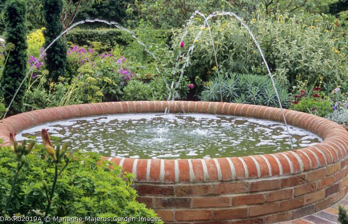 Raised circular fountain of red brick