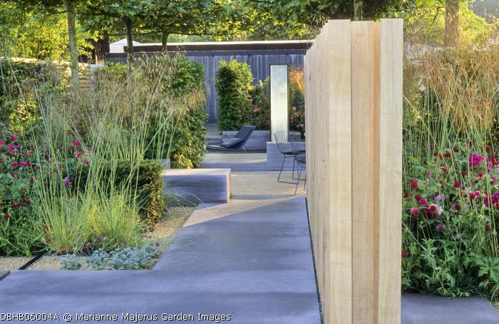 Oak screen, basalt paving, Stipa gigantea, chairs in enclosed sunken patio