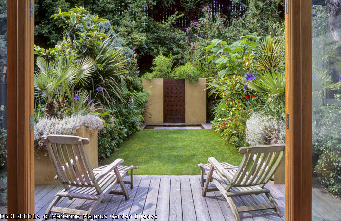Wooden chairs on decking overlooking small exotic town garden, water wall focal point
