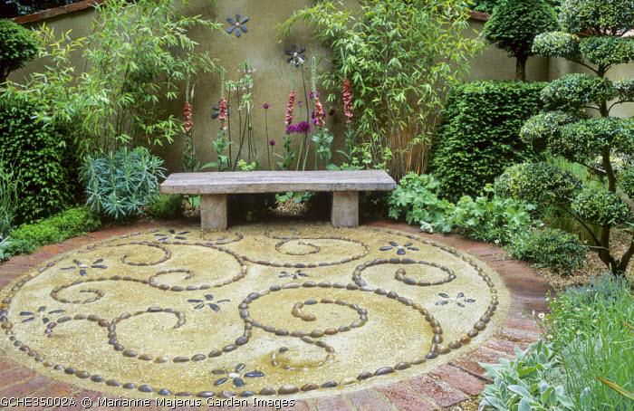 Circular patio, pebble and shell mosaic paving pattern, stone bench, cloud-pruned Ilex crenata, verbascum, yew topiary, bamboo