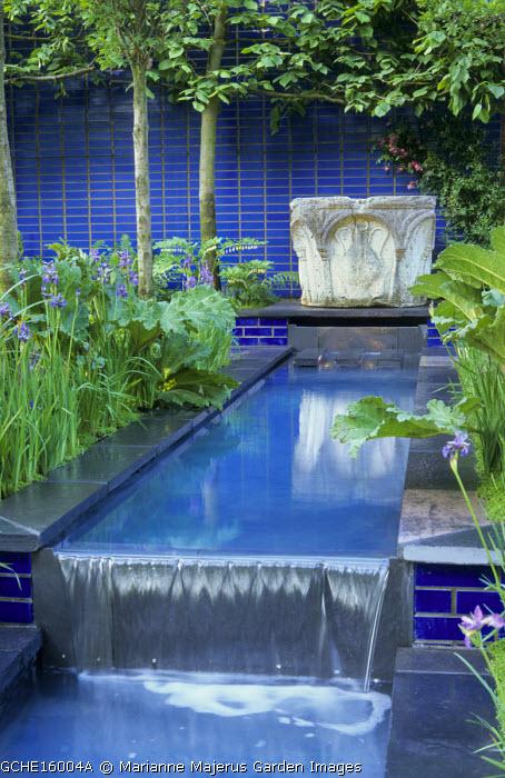 Stone well fountain on patio, blue ceramic tiles, formal canal, Iris sibirica