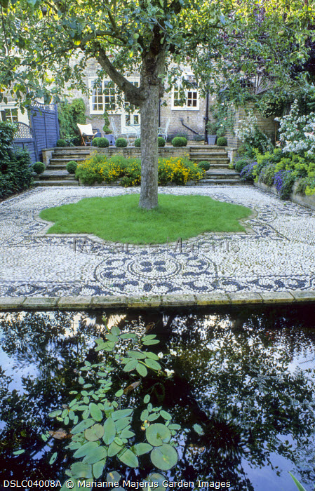 View across reflective rectangular pond to house, pebble mosaic by Michael Gough, apple tree, Aponogeton distachyos, Water hawthorn