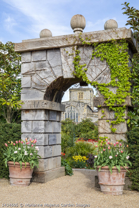 Stone archway, tulips in large terracotta pots, view to cathedral