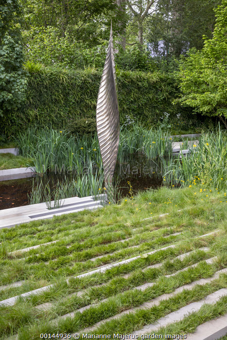 Bronze sculpture, Nyneve in formal pool, Iris pseudacorus, stone and grass terrace