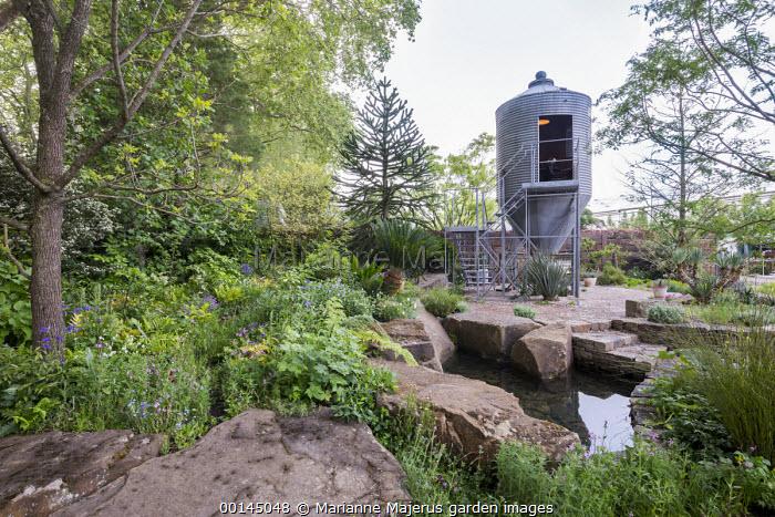 Grain silo repurposed as a design studio office, pond within large rocks, Araucaria araucana, path through woodland garden, lychnis, aquilegia, geraniums, Cycas revoluta