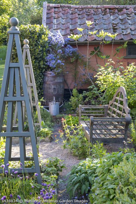 Wooden bench in herb garden, wooden obelisks, Allium schoenoprasum, ceanothus, Centranthus ruber