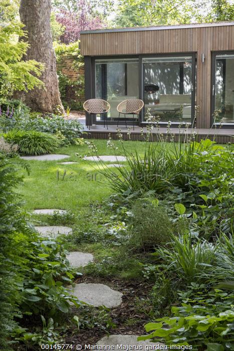 Stepping stone path across lawn, Hakonechloa macra, Libertia grandiflora, chairs on terrace by contemporary cedar studio pavilion by Ecospace